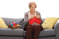 Femme mûre s'asseyant sur un sofa et un tricotage Photographie stock