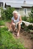 Femme mûre s'asseyant sur une chaise de son jardin Photographie stock libre de droits