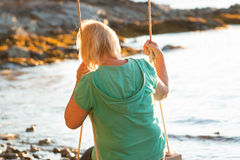 Femme mûre se reposant sur l'oscillation à la plage Images libres de droits