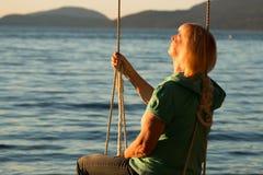 Femme mûre se reposant sur l'oscillation à la plage 2 Image libre de droits