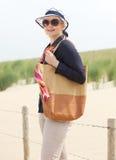 Femme mûre se tenant à la plage avec le sac et les lunettes de soleil Images stock