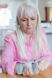 Femme mûre souffrant de la blessure de poignet à la maison photo stock