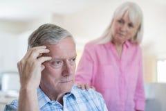 Femme mûre soulageant l'homme avec la dépression à la maison photos libres de droits