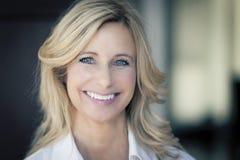 Femme mûre souriant à l'appareil-photo Photo stock