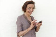 Femme mûre souriant et textotant Photo libre de droits