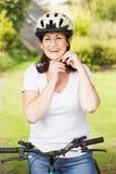 Femme mûre sur le tour de cycle dans la campagne Images libres de droits