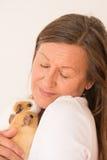 Femme mûre tenant des animaux familiers de cobaye Photographie stock libre de droits