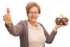 Femme mûre tenant un petits panier et pouce  Images stock