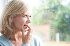Femme mûre triste souffrant de l'agoraphobie regardant hors de Windo image libre de droits