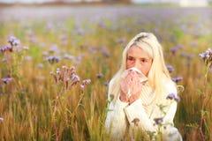 Femme mûrie avec le mouchoir et allergie dans un domaine de fleur Photographie stock