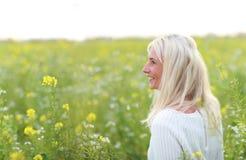 Femme mûrie heureuse dans le flowerfield Photos stock