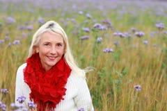 Femme mûrie heureuse dans le flowerfield Image stock