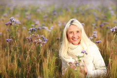 Femme mûrie heureuse dans le flowerfield Photographie stock