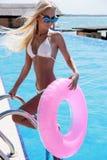 Femme magnifique avec les cheveux blonds dans le maillot de bain élégant posant près de la piscine photographie stock libre de droits