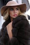 Femme magnifique avec les cheveux blonds dans le manteau de fourrure et le chapeau luxueux photographie stock