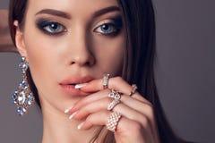 Femme magnifique avec les cheveux foncés et maquillage lumineux avec le bijou luxueux images stock