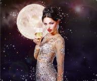Femme magnifique avec un verre de champagne sur le fond d'a Images libres de droits