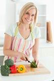 Femme magnifique coupant le poivre vert Photos stock