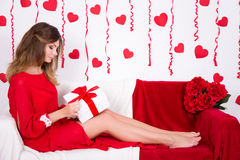 Femme magnifique dans le boîte-cadeau rouge d'ouverture de robe dans la chambre décorée W Photographie stock libre de droits