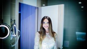 Femme magnifique de brune avec de longs cheveux et yeux bleus se regardant dans le miroir images stock