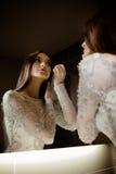 Femme magnifique de brune avec de longs cheveux et yeux bleus se regardant dans le miroir et faisant le maquillage photographie stock