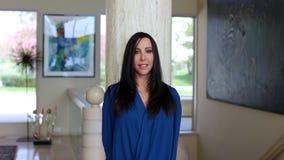 Femme magnifique de cheveux sombres souriant avec la belle chemise bleue, psychologue professionnelle dans une salle d'art déco images libres de droits