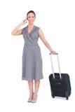 Femme magnifique de sourire portant sa valise ayant l'appel téléphonique Photos stock