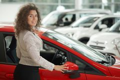 Femme magnifique posant près de la voiture rouge au centre de voiture images stock