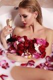Femme magnifique sexy avec les cheveux blonds détendant dans la salle de bains avec des pétales de rose, champagne potable Image stock