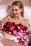 Femme magnifique sexy avec les cheveux blonds détendant dans la salle de bains avec des pétales de rose, champagne potable Image libre de droits