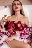 Femme magnifique sexy avec les cheveux blonds détendant dans la salle de bains avec des pétales de rose, champagne potable Photo stock