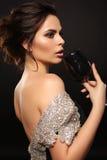 Femme magnifique sexy avec les cheveux foncés jugeant en verre avec le cavi noir image libre de droits