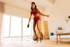 Femme maigre avec le corps de sport sautant la corde dans la chambre à coucher images stock