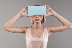 Femme maigre résolue avec la coupe de cheveux de plomb plaçant le carton bleu sur son visage photo libre de droits