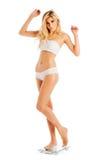 Femme maigre se tenant sur des échelles de salle de bains. Photo libre de droits