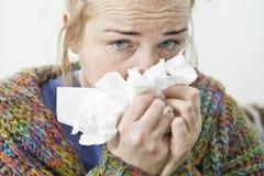 Femme malade à la maison éternuant dans le tissu Photographie stock libre de droits