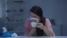 Femme malade éternuant et buvant du thé chaud par temps pluvieux, épidémie de virus de grippe banque de vidéos