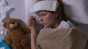 Femme malade avec la serviette sur le front et l'écoulement nasal étreignant l'ours de nounours dans le lit, grippe clips vidéos