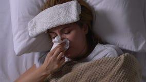 Femme malade avec la serviette sur le front se situant dans le lit, toussant et nez de soufflement, grippe banque de vidéos