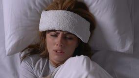 Femme malade avec la serviette sur le front tremblant avec le froid dans le lit, symptômes de grippe banque de vidéos