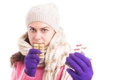 Femme malade avec le chapeau tricoté et l'écharpe tenant des pilules images libres de droits