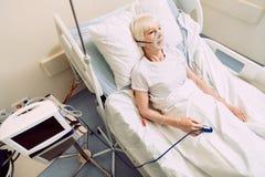Femme malade avec le matériel médical de fréquence cardiaque et l'appui respiratoire Image libre de droits