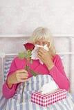 Femme malade dans le lit avec des roses et des tissus Photographie stock libre de droits