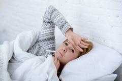 femme malade dans le lit vérifiant la température avec le virus froid de grippe d'hiver de douleur faible fébrile de thermomètre Photographie stock