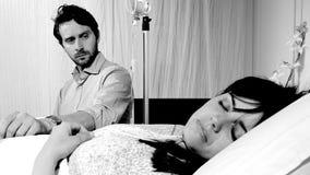 Femme malade dormant dans l'hôpital tandis que le mari la regarde noire et blanche Photographie stock