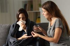 Femme malade et son ami donnant la pilule de calmant Image libre de droits