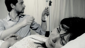 Femme malade malade pleurant dans l'hôpital tandis que le mari prend soin de elle Photographie stock libre de droits
