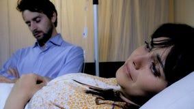 Femme malade pleurant dans l'hôpital tandis que le mari dort Photo libre de droits