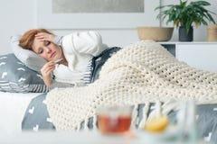 Femme malade regardant le thermomètre image libre de droits