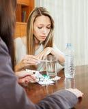 Femme malade regardant par le thermomètre, amie l'aidant Photo libre de droits